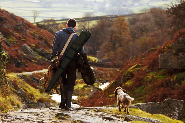 Un chasseur et son chien, de dos, rentrant de la chasse son gibier à la main